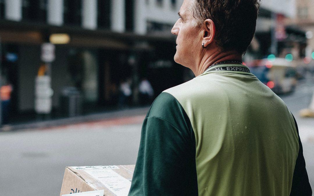 Briefzusteller von hintern, Paket in den Händen, steht an Straßenrand