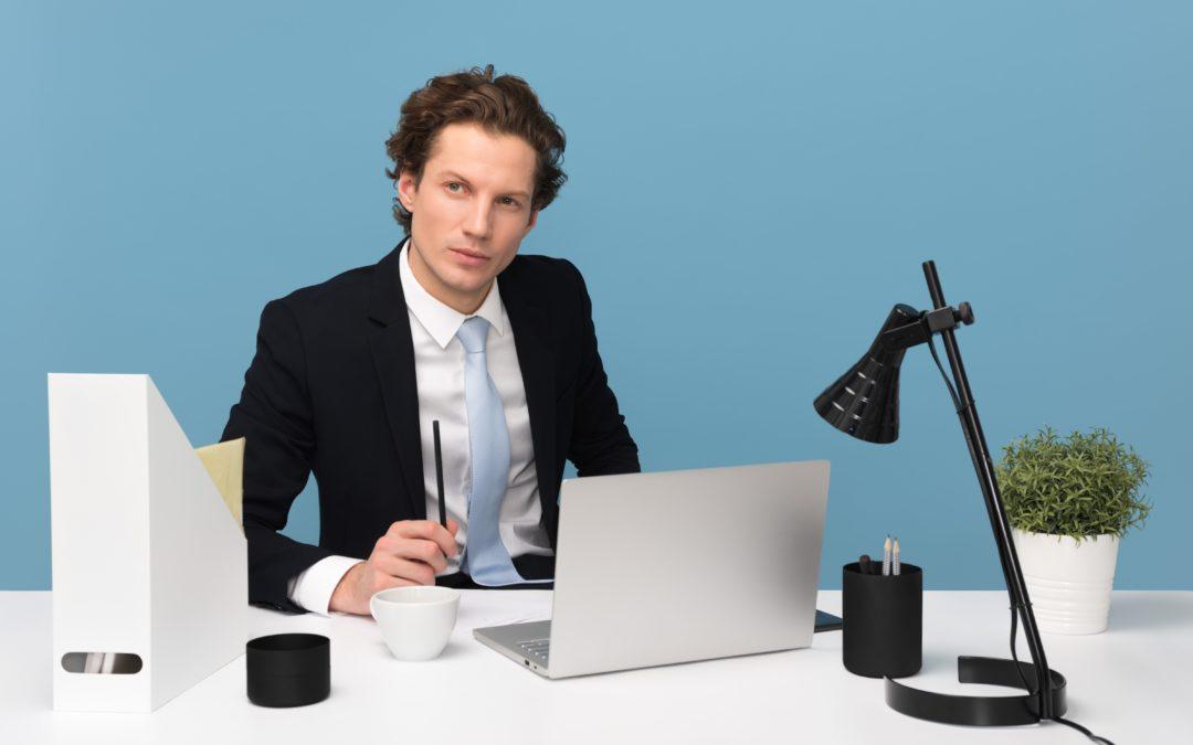 Young Professional, blaue Wand, weißer Schreibtisch, konzentrierter Blick