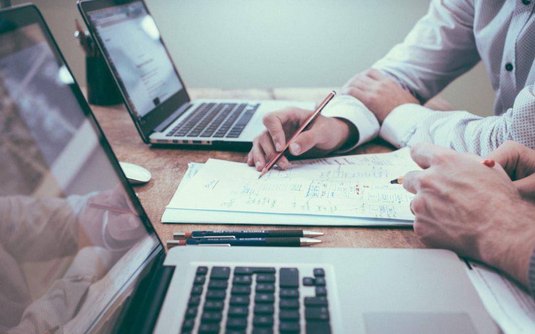 Schreibtisch, zwei Laptops, Buchhalter erklärt Geschäftszahlen